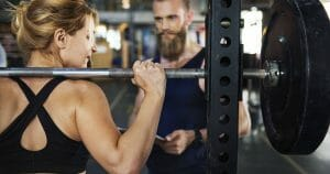 women about to squat with male trainer